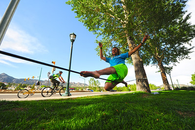 Walt Hester | Trail Gazette Trevor Hunt, a Camp Timberline attendee from Grand Rapids, Mich., balances on a slack line as local Danny Basch pedals by on Elkhorn Avenue on Wednesday. Not all of Estes Park's recreation happens in the parks or ball fields.