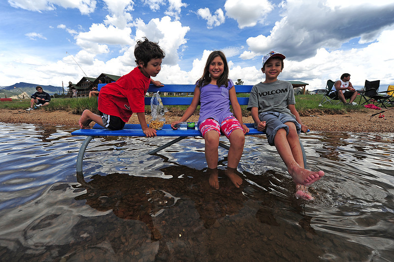 Walt Hester | Trail Gazette<br /> From left, Emanuel Camacho, 5, Marissa Murphy, 9, both from Ft. Morgan, and Gerdencio Villarreal of Greeley dip toes into Lake Estes on Satruday as clouds gather. By the afternoon, thurnder was rumbling across the valley, while severe weather was expected along the Front Range.