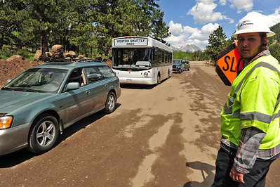 Walt Hester | Trail Gazette Chance Myers checks for the pilot vehicle as traffic begins to pile up at the start of Bear Lake road on Monday. Drivers who wish to use their own cars can expect at least a 40-minute delay due to construction on the road.
