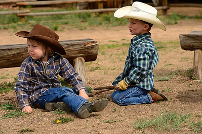 Walt Hester | Trail Gazette Little buckaroos Owen Evens, 4, left, and Haslee Rasmussen, 3, play in the MacGregor Ranch corral on Tuesday. The boys were waiting for the annual spring branding to begin.