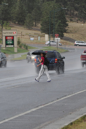 Walt Hester | Trail Gazette<br /> A pedestrian makes her way across Big Thompson Avenue in Wednesday's much-needed rain. Rain continues in the forcast for Friday.
