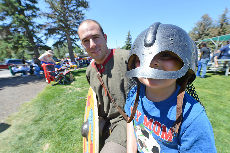 Walt Hester | Trail Gazette<br /> Noah Clark, 4, peeks out from under the helmet of fight captain Craig Brice of Denver. Brice and others from the Fjellborg Vikings re-enact the lives of the Norse people from centuries ago.