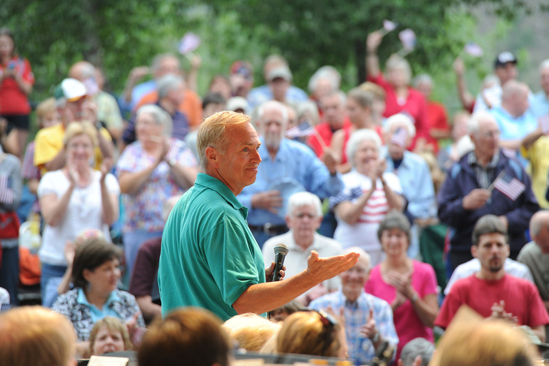 Walt Hester | Trail-Gazette<br /> Scott Anderson solutes the Village Band after singing the National Anthem to begin the annual Patriotic Concert on Wednesday. The concert drew a large croud of music lovers to Performance Park.