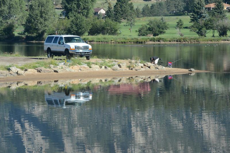 A fisherman checks his tackle box while fishing the calm water of Lake Estes Monday morning.