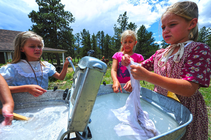 Walt Hester | Trail Gazette<br /> From left, Dianna Patrick, 7, reese Nicholes, 9, and Julia Patrick, 10, wash laundry the really old-fashioned way at the MacGregor Ranch Heritage Camp on Wednesday. Campers get to cook, clean and play as kids did 100 years ago.