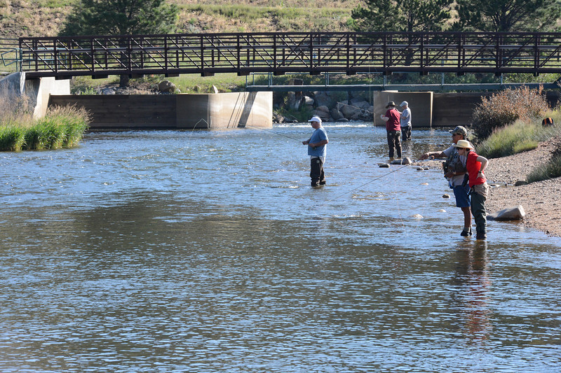 Fishermen ply the waters of the Big Thompson River just below the Olympus Dam spillway.