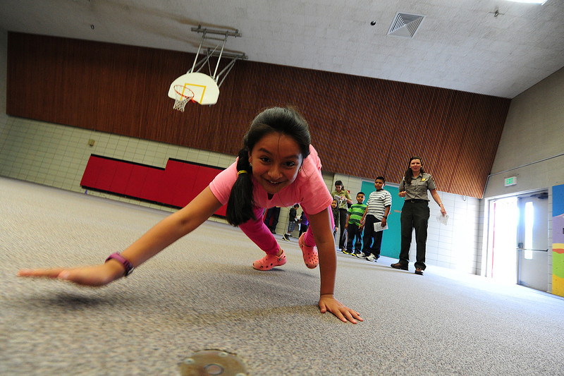 Walt Hester | Trail Gazette<br /> Maria Rojas, 9, scampers across the old elementary school gym like a black bear on Wednesday. The Kids Cafe offerts learning activities for children, as well as a nutricious lunch.