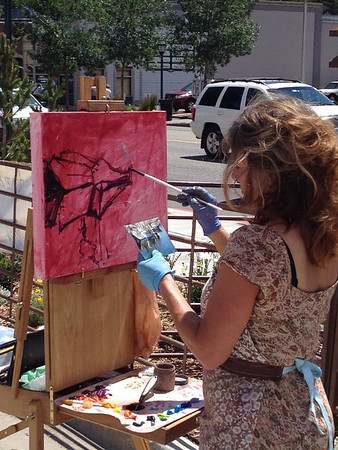 An artist paints from a photograph Saturday morning during the Estes Park Summer Fest sponsored by the Longs Peak Rotary Club. The three-day event in Bond Park included music, food and drink.
