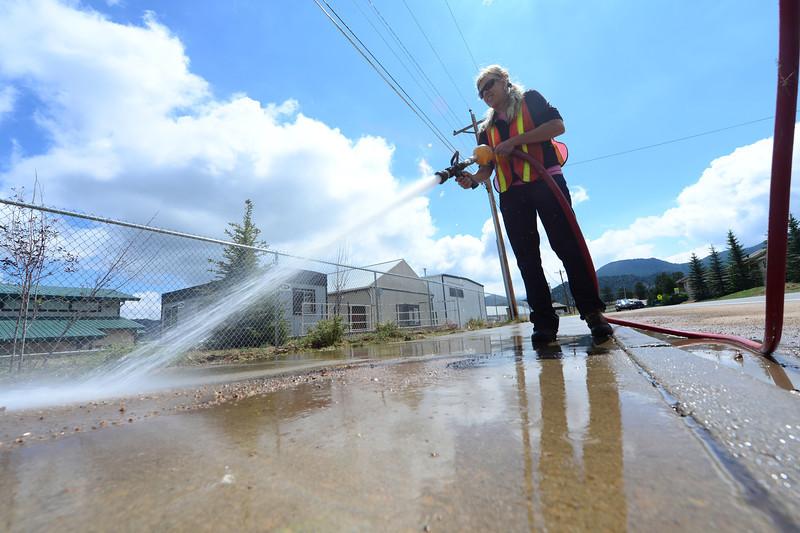 Walt Hester | Trail-Gazette<br /> Tonya Ziegler sprays debris off of the sidewalk at the Stanley Fairgrounds on Monday. Clean up after heavy weekend rain kept crews in Estes Park busy.