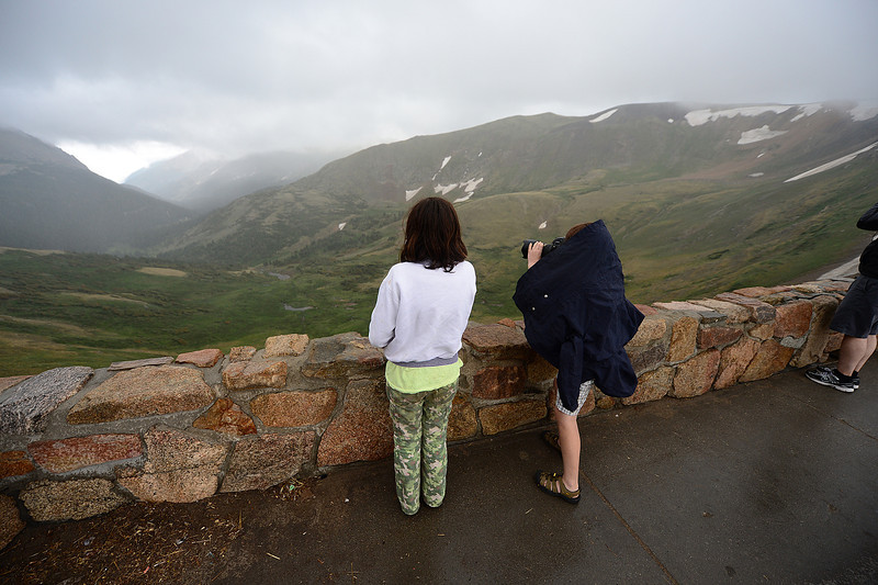 Walt Hester | Trail-Gazette<br /> Children photograph the headwaters of the Fall River from the Alpine Visitor Center as clouds lift and rain falls on Saturday. Temperatures dropped 12 degrees in 30 minutes as rain began to fall above treeline.