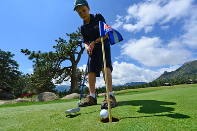 Walt Hester | Trail-Gazette Amos Westley, 12, knocks in a practice putt at the Estes Park Public 18-whole course on Monday. In spite of recent rain, the course is open for business.