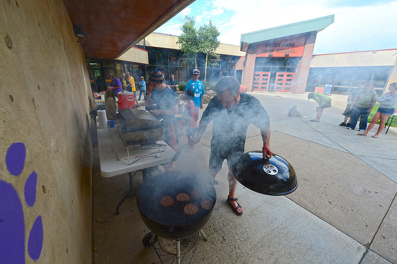 Walt Hester | Trail-Gazette<br /> Parents cook while everyone eats at the annual Estes Park High School marching band end-of-summer cookout at the school. The band has practiced throughout the summer.