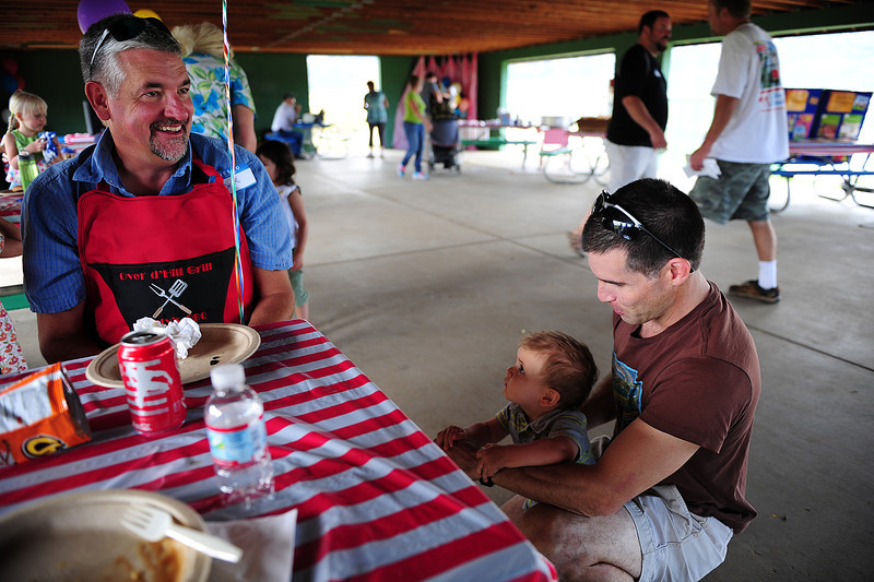 "Walt Hester | Trail-Gazette<br /> Dr. Martin Koschnitzke enjoys the company of nine-month-old Gabe Sanchez and father Ben, at the New Life Center Picnic on Saturday. Dr. ""K"" delivered a majority of the children at the picnic."