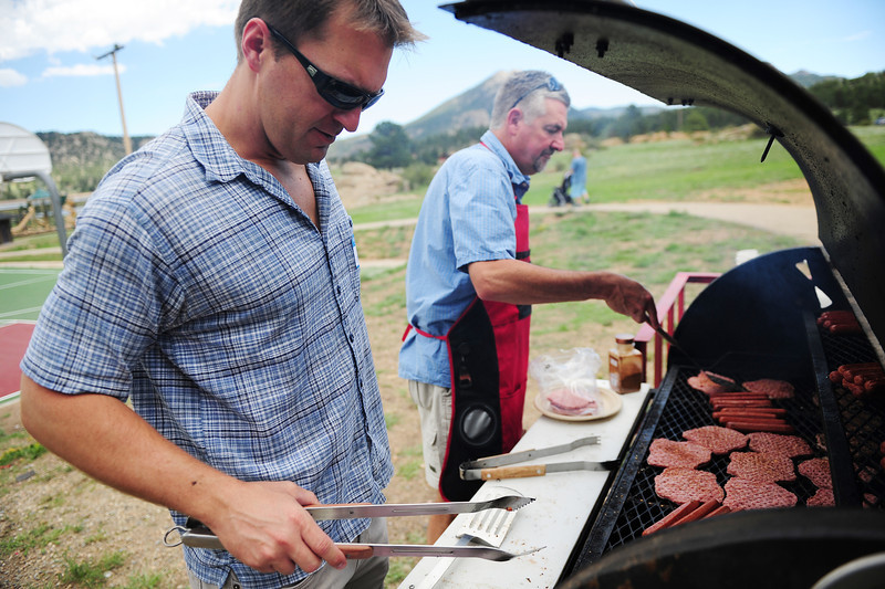 Walt Hester | Trail-Gazette<br /> Doctors Josh Timock and Martin Koschnitzke take charge of the grill at the picnic. The doctors are the before and after of the child-birthing process at the EPMC.
