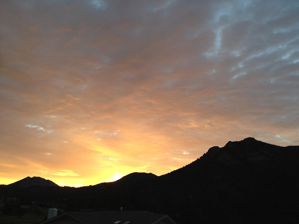 The rising sun seems to put fire into the morning clouds over Estes Park on Thursday. Another morning of sun and clouds is predicted, followed in the afternoon by a good chance of isolated storms and a high in upper 70s.