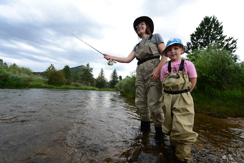 Walt Hester | Trail-Gazette<br /> Carrie Tholstrup and daughter, Clare, 5, of Bison, Kans. fly fish in the Big Thompson River below the Olympus Dam on Wednesday. The afternoon rain doesn't discourage the diehard anglers, no matter the age.