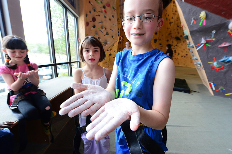 Walt Hester | Trail-Gazette<br /> Kade Ludlam, 9, shows off his chalked hands before he shimmies up the climbing wall at the Estes Park Mountain Shop on Wednesday. The indoor wall was a great indoor activity for the gaggle of children as the afternoon showers rolled in.
