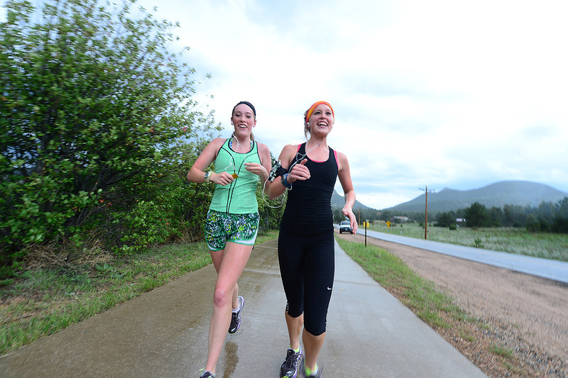 Walt Hester | Trail-Gazette<br /> Running sisters Brenna, left, and Delaney McFadden of Kearney, Nebr. splash along the Lake Estes Trail in the afternoon rain on Wednesday. WHile rain came hard and cold, it was brief.