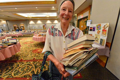 Walt Hester | Trail-Gazette Alice Fox, a summer resident, carries an armload of books in the Estes Valley Public Library used book sale on Saturday. The sale filled the main hall of the Estes Park Conference Center.