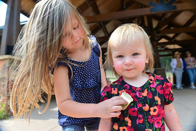 Walt Hester | Trail-Gazette Charlotte McCoy, 4, of Des Moines, Iowa, pins a Junior Ranger badge on sister Gemma, 1, in Hidden Valley on Wednesday. The warming house in Hidden Valley is the headquarters for the national park's Junior Ranger Program.