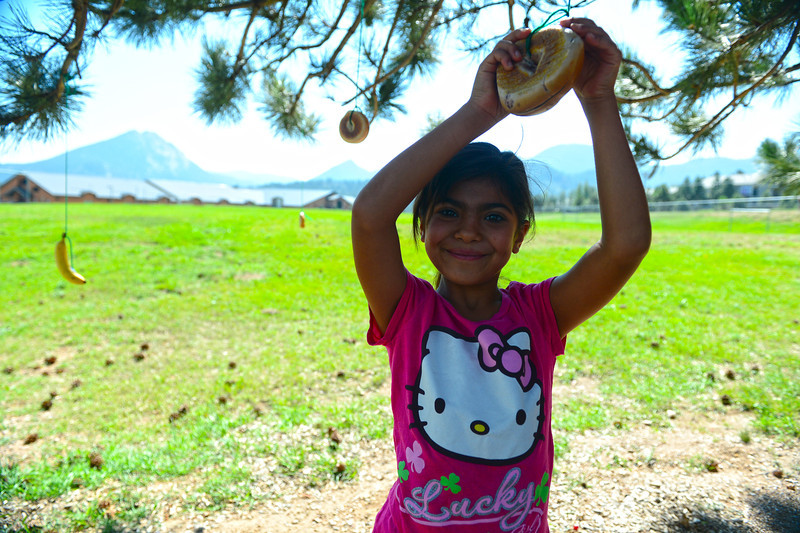 Walt Hester | Trail-Gazette<br /> Andrea Garcia, 7, pulls a bagel from a tree at the elementary school playground on Saturday. The event was a jungle breakfast for students of teacher Ann Leija.
