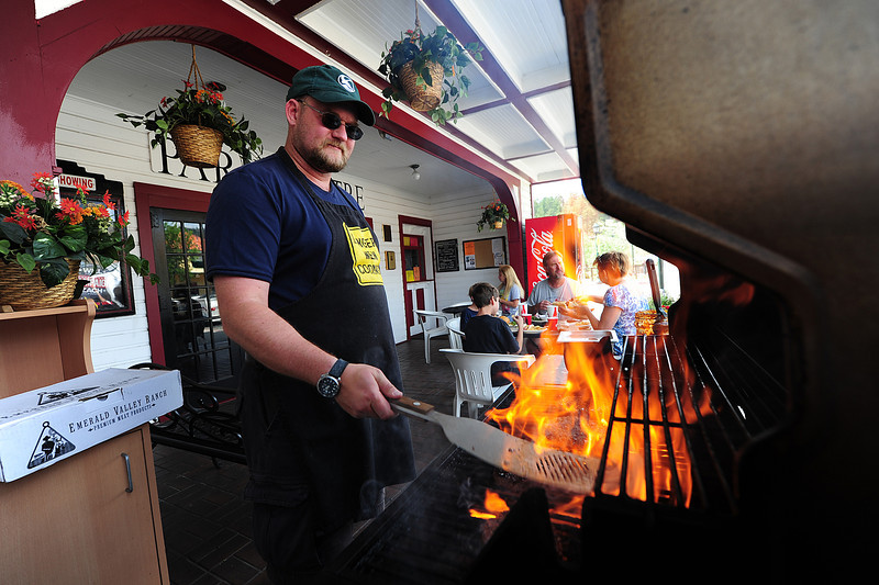 Walt Hester | Trail-Gazette<br /> Jake MacGregor works the grill at the Park Theatre Cafe on Sunday. The pleasant temperatures and smells drew visitors to eat in front of what is now the oldest opperating movie theatre in the nation.