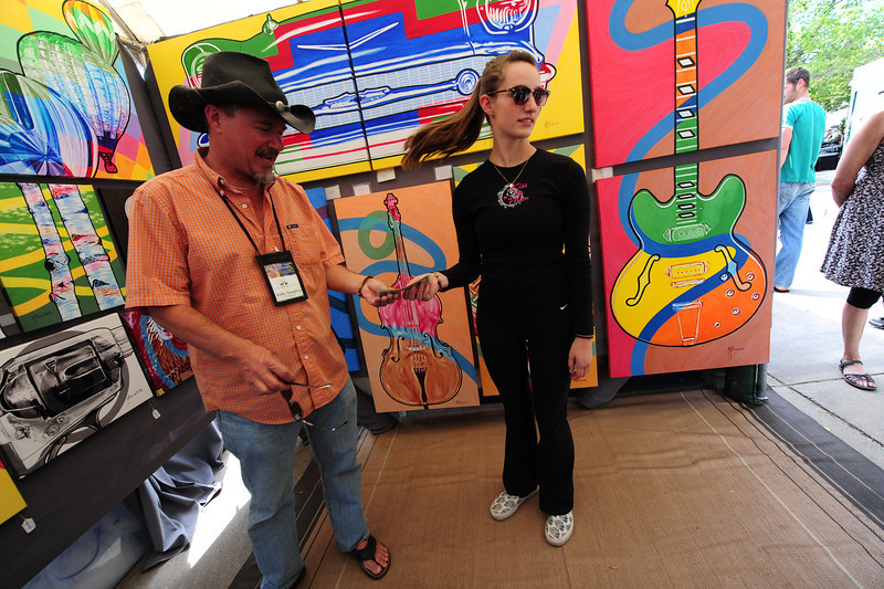 Walt Hester | Trail-Gazette<br /> Erin Diedrich of Estes Park pays artist Andy Quaglino of Conifer for one of his pieces. The market offers artists the chance to sell work and gain exposure.