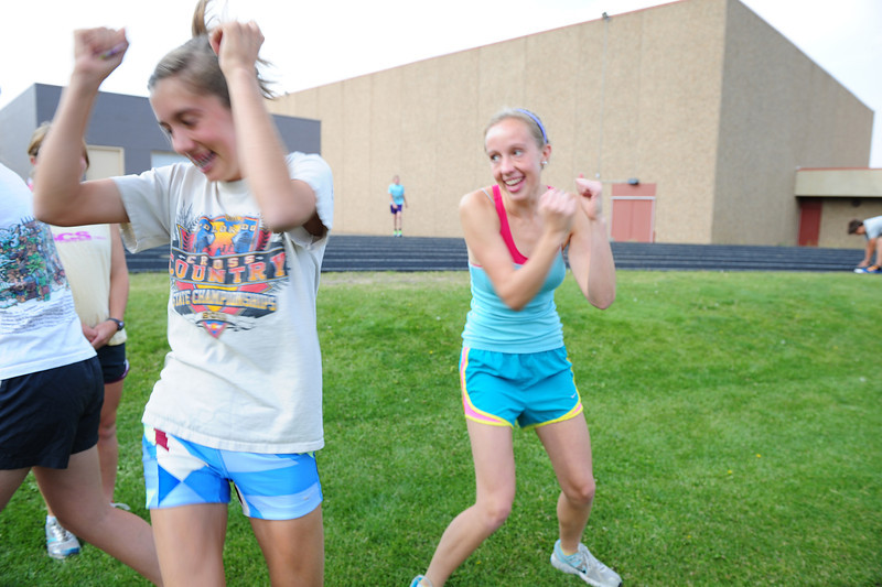 Walt Hester   Trail-Gazette<br /> Kelsi Lasota, left, and team mate Holli Holmes dance briefly before warmups at Wednesday's croos-country workout. Lasota has plenty to make her dance as she won the 35th annual Liberty Bell Invitational last weekend.