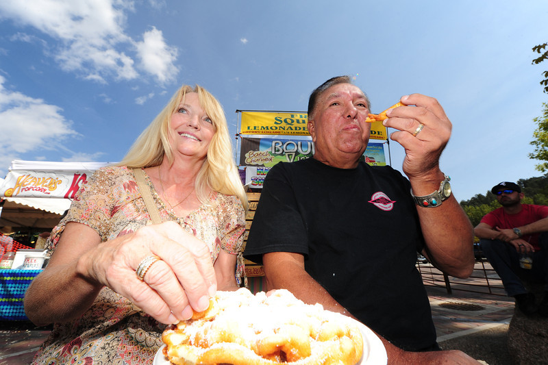 Walt Hester | Trail-Gazette<br /> Melody and Robert Bryant of NcAllister, Okla. enjoy funnel cake at Autumn Gold on Saturday. While beers, bands and brats were the theme, visitors had other options for festive sweets.