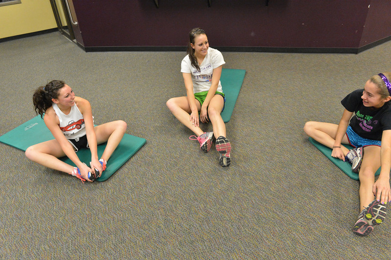 Runners, from left, Bizzy Palmer, Erin Barker and Kelsie Lasota stretch before their Wednesday workout at the Estes Park High School. It's never too early to look forward to spring, if you are a runner.