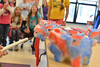 Red, white and blue pigs dive off of a table in the Estes Park Elementary School cafeteria on Wednesday. Top ABC fundraisers from each grade were awarded for their efforts with the pigs and racing.