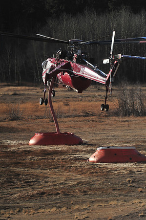 "A large sky crane helicopter drops its snorkle into a ""pumpkin"" or mobile water tank in Upper Beaver Meadows on Monday. The helicopters can pull in several thousand gallons of water in about 30 seconds."