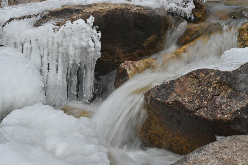 The Roaring River makes its way around rocks and ice on Wednesday. The combination of water and ice slowly turns the big boulders and rocks into dirt and sand.