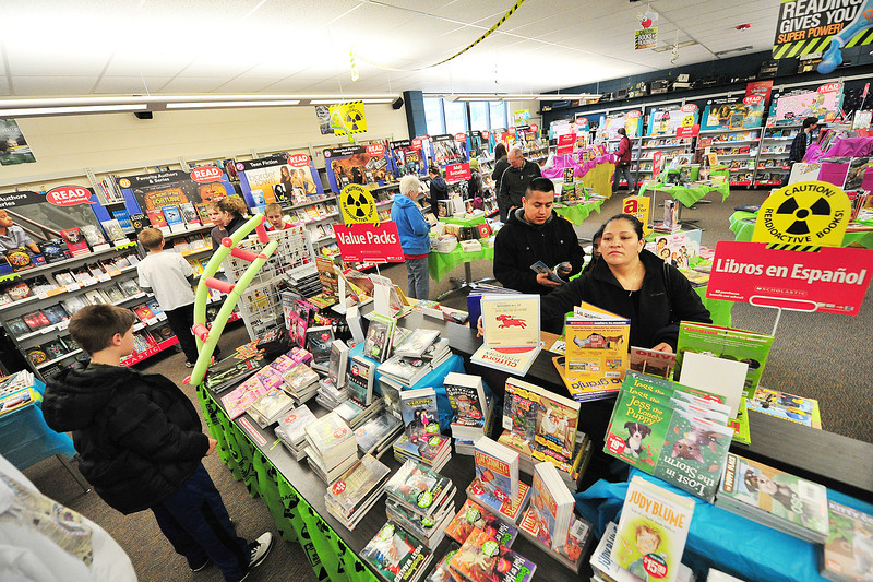 Parents and children wander the shelves of the Estes Park Middle School Library on Thursday. The school sponsored their annual book fair last week, exposing readers to more titles.