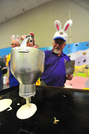 Mike Oline squeezes out pancake batter on Saturday morning at the Breakfast with the Easter Bunny at the old elementary school gym. The Lions Club stepped in to make breakfast for the event.