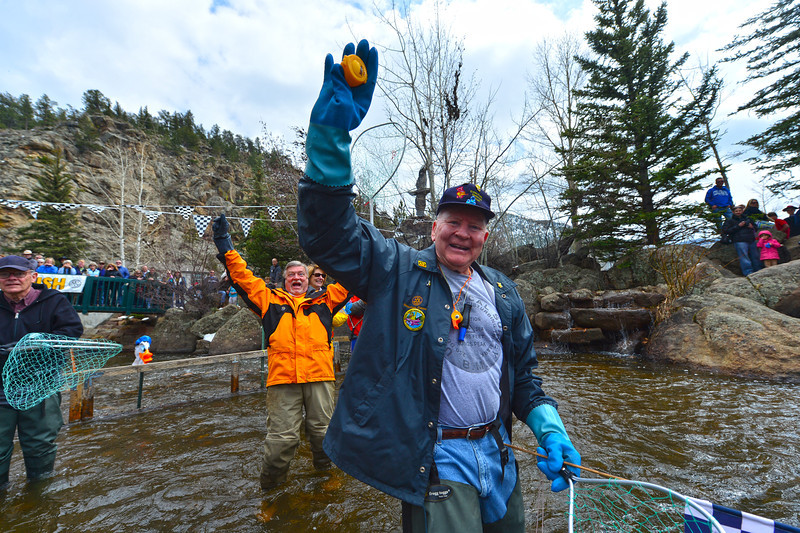 Tom Maher holds up the winning duck at the Riverside Plaza finish line on Saturday. Maher has fished the winner out of the river all but one duck race, so far.