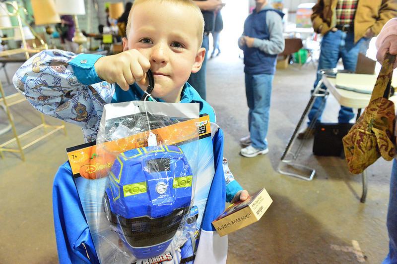 Noah Rau, 4, of Imperial, Nebraska, scores a new costume atthe annual Crossroads Garage Sale at the Stanley Fairgrounds on Saturday. The event raises funds for the charitable group.