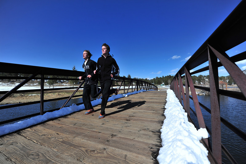 High school runners Tanner Stark, left, and Noah Purdy dash over a bridge along the Lake Estes Trail on Wednesday. The high-altitude 'Cats are traditionally good runners over most distances in track, though tend to excel as the races lengthen.