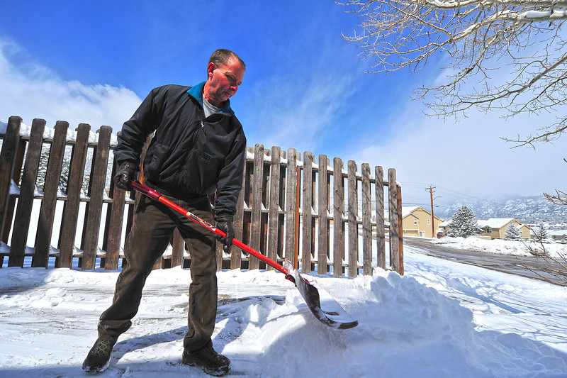John Paulos clears snow away from the back door of the Estes Park Aquatic Center on Tuesday. Some areas of Estes Park received eight inches of snow from the latest storm, cancelling school and all of the day's school-related activities.