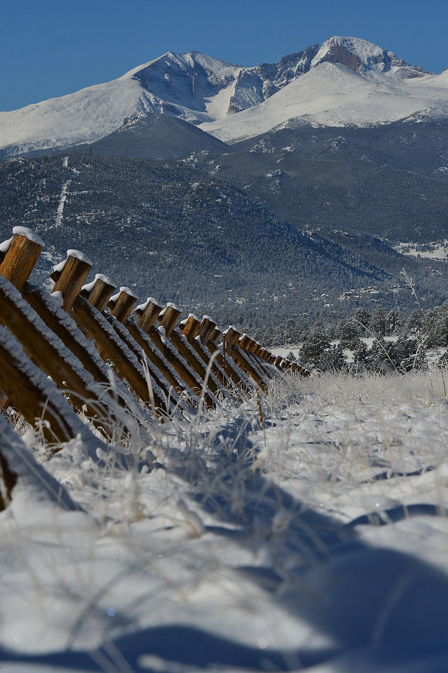 A traditional buck and rail fence leads the way down Devils Gulch Road on Wednesday. New snow beautified the landscape but did little to ease the current drought.