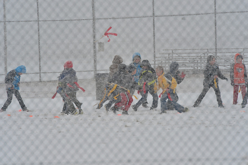 Flags fly with flakes during a football game on Tuesday. Snow was no deterrent for football enthusiasts.