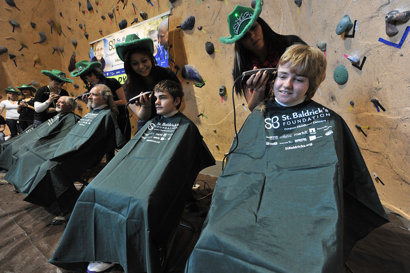 The Chrastil family gets shaved. From right, Carleigh, Bert and Mark, made the event a family outing as Carleigh declared this her last year getting the St. Baldrick's treatment.