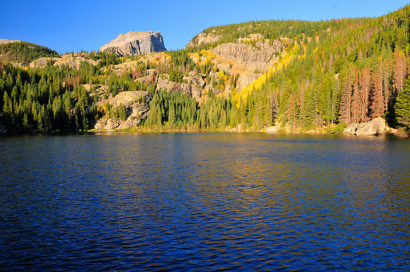 Photo by Walt Hester<br /> Gold, green and blue reflect off of the surface of Bear Lake on Tuesday. While the weather is changing, leaves are hanging on inthe park.