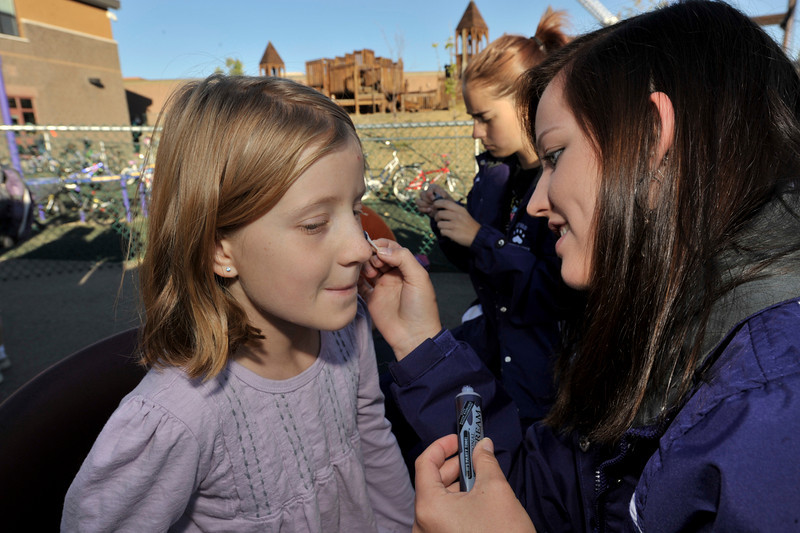 Photo by Walt Hester<br /> BellaLibby, 9, gets some artistic attention from Estes Park High School Cheerleader Sena Krula, 14, during the walkabnd ride to school day at the elementary school on Wednesday.