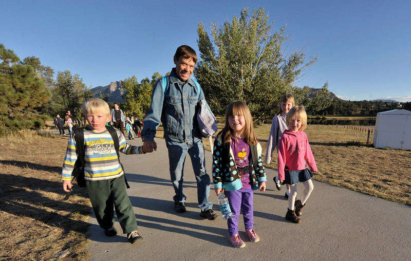 Photo by Walt Hester<br /> A group of children and a father walk along the Lake Estes trail on Wednesday. The elementary school sponsored a Walk and Ride to School Day with helthy snacks, free bicycle helmets, face painting and visits from the equipment of the fire authority and EMTs from the hospital.