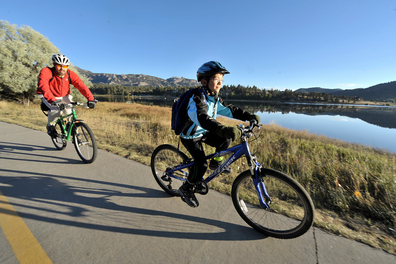Photo by Walt Hester<br /> Geo Dumont, right, and father, Frank, ride mountain bikes along the Lake Estes Trail on Wednesday. The Estes Park Elementary School was promoting better health and fitnes by spocering a ride and walk to school day.