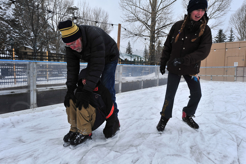 Gary Matthews of Estes Park, pushes Corbin Matthews, 13, of Thornton while cousin Grace Marks of Aptos, Calif., skates by at the Estes Park Ice Rink on Tuesday. The rink and the twon attracted visitors from the Front Range, the Deep South and the Left Coast.