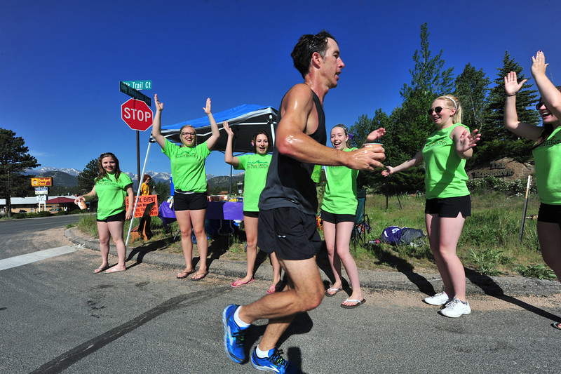 Estes Park High School cheerleaders shout for a runner at the crest of the Big Thompson Avenue climb on Sunday. Many different volunteers and organizations took up the call for aid station volunteers on Sunday, helping runners with snacks and hydration along the race route.