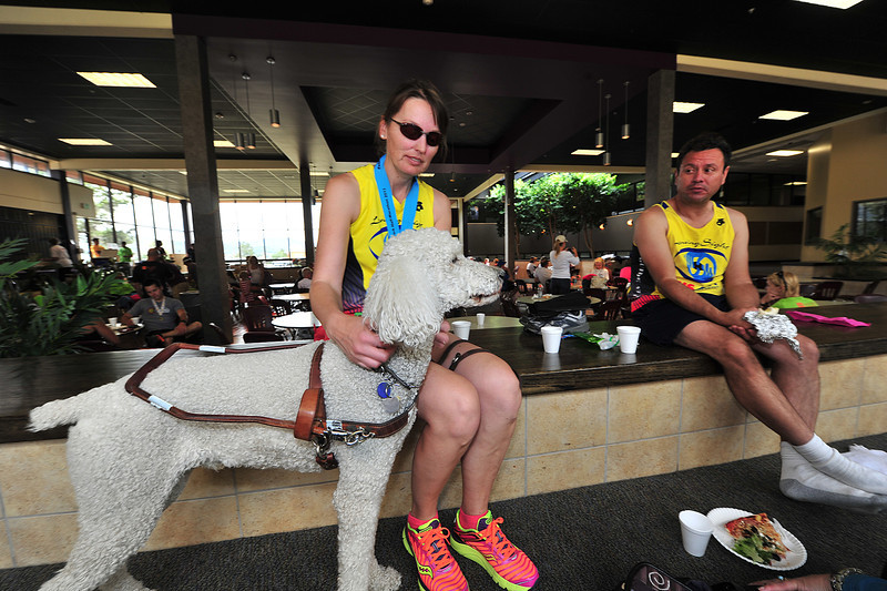 Penn Street and her service dog, Boo, relax with running guide, JR Zundel, relax after finishing the half marathon on Sundy.Street was one of several visually impared runners to compete on Sunday.