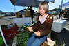 Marilyn Cockroft, 9, of Croft Family Farm peels garlic scapes at Thursday morning's Estes Valley Farmers' Market. The market offers a fmily experience, as well as produce a locally-made products.